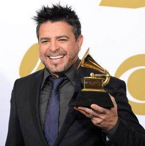 Latin music singer Luis Enrique holding a Grammy.